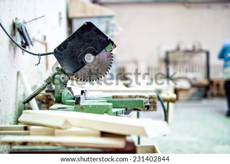 industrial tool in wood and metal factory, compound mitre saw with sharp, circular blade  - stock photo