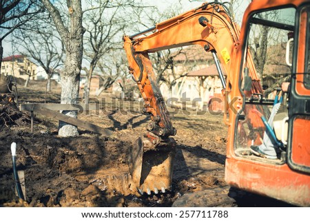 Industrial truck loader excavator leveling earth and ground hole at house construction site. Vintage effect - stock photo