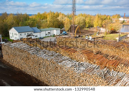 Industrial warehouse - huge heaps with pulpwood ready for transportation - stock photo