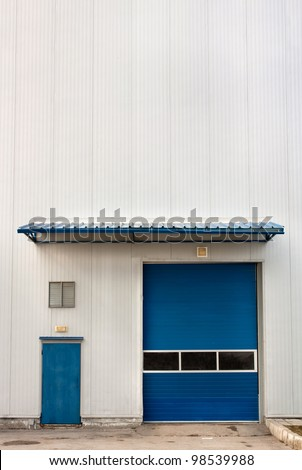 Industrial Warehouse Unit with blue  roller shutter door.Copy space - stock photo