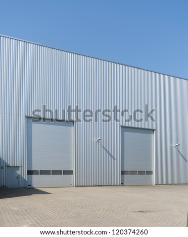 industrial warehouse with double roller doors - stock photo
