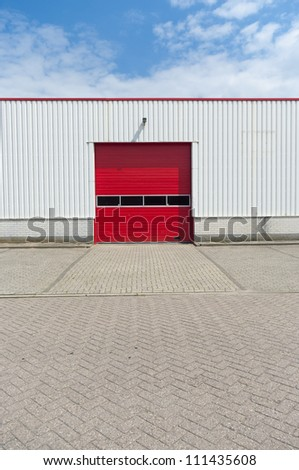 industrial warehouse with red roller door - stock photo