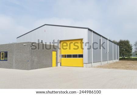 industrial warehouse with yellow roller door - stock photo