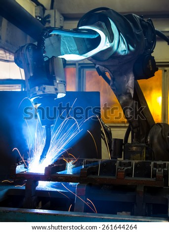 Industrial welder robotic in a car factory - stock photo