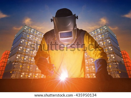 Industrial welding worker with safety equipments and protective mask welding steel structure with cargo container stack in background for transportation import,export and logistic industrial concept - stock photo