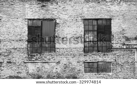 Industrial white heavily damaged factory brick wall with broken windows.  - stock photo