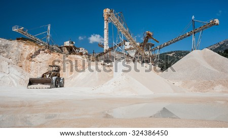 Industrial work processing of stones with a gravel sorter machinery reflected in water at a quarry with a clear blue sky - stock photo