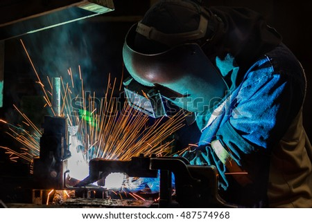 Industrial Worker at the factory welding metal ,closeup