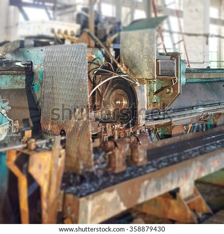 Industrial worker cutting and welding metal. Rolling mill machine. Tilt shift effect - stock photo