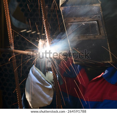 Industrial worker cutting and welding metal with many sharp sparks - stock photo