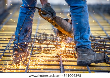 industrial worker cutting steel, sawing reinforced bars using angle grinder mitre saw - stock photo