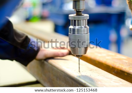 industrial worker drilling a hole with automatic drill machine in a metal bar - stock photo
