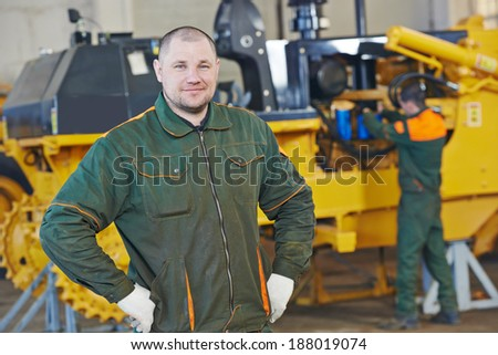 industrial worker during heavy industry machinery assembling on production line manufacturing workshop at factory