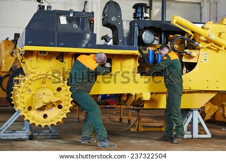 industrial worker during heavy industry machinery assembling on production line manufacturing workshop at factory - stock photo