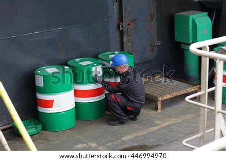 Industrial worker inspecting barrels in industrial plant