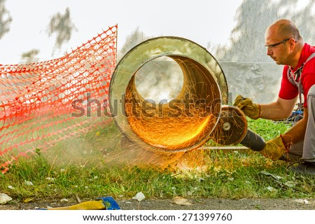 Industrial worker on construction site is grinding to cut a huge pipe wearing his protective glasses. - stock photo