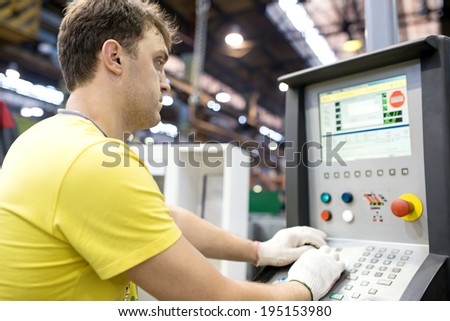 Industrial Worker operator entering data in CNC machine at Factory Workshop - stock photo