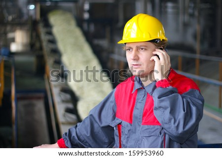 Industrial worker talking on cell phone - stock photo