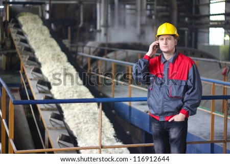Industrial worker talking on cell phone at the factory for the production of food - stock photo