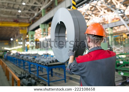 Industrial worker transporting transformer steel cargo with workshop rail mounted gantry overhead crane - stock photo