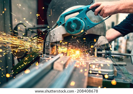 industrial worker using a  compound mitre saw with circular blade for cutting metal and plastic - stock photo