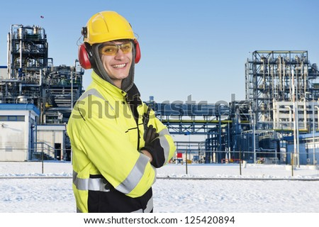 Industrial worker wearing all safety clothing necessary, such as hearing protection, a hard hat, chemical resistant reflective coat, gloves and safety glasses. Proudly smiling into the camera - stock photo