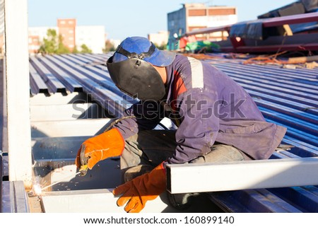 Industrial worker welder in workwear and mask during roofing works by means of inverter welding machine - stock photo