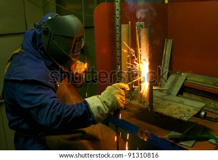 Industrial Worker Welder welding metal at factory workshop with flying sparks - stock photo