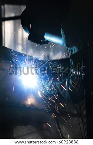 Industrial worker welding in factory - stock photo