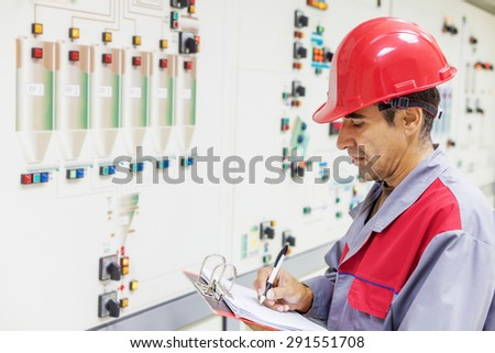Industrial worker writes on a paper conditions from a control panel.Shallow doff - stock photo