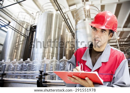 Industrial worker writes on a paper conditions in a filling line production of drinking water.Shallow doff - stock photo