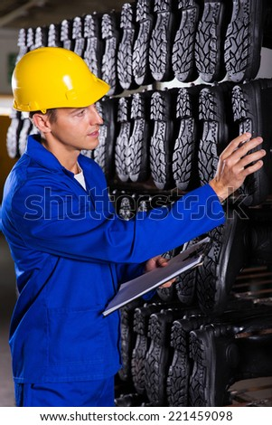 industrial workers checking gumboots sole in storehouse - stock photo