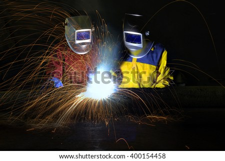 Industrial workers cutting and welding metal with many sharp sparks, - stock photo