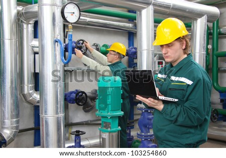 Industrial workers with notebook, teamwork - stock photo