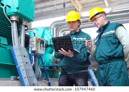 Industrial workers with notebook working in a power plant, teamwork - stock photo