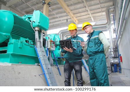 Industrial workers with notebook working in power plant, teamwork
