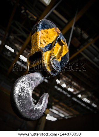 Industrial yellow crane hook - stock photo