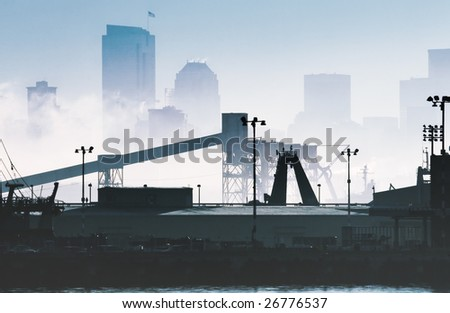 Industrial zone in the morning fog with the skyline in the background - stock photo