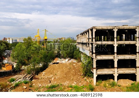 Industrial zone with concrete damaged building on the foreground and new modern buildings on the background. Construction industrial concept.   - stock photo