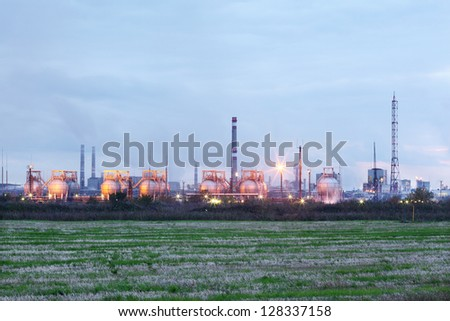 Industrial zone with factories and pipes with smoke and illumination at evening.