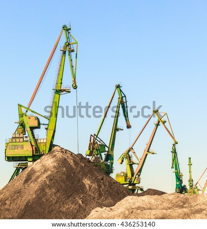 Industry equipment technology cargo commerce transport concept. Cranes in morning harbour. Industrial machines working in port facility. - stock photo