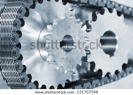 industry gears and cogs powered by large timing chain, blue toning concept - stock photo