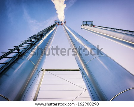 industry smoke stacks in front of blue sky - stock photo