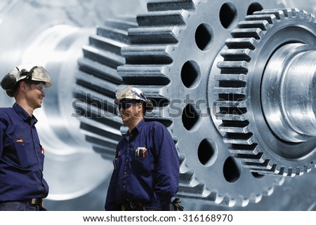industry workers, engineers with giant cogwheels and gears axles, steel industry - stock photo