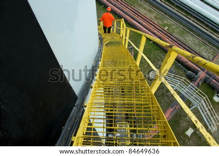 industry workers using yellow stairs after inspection process - stock photo