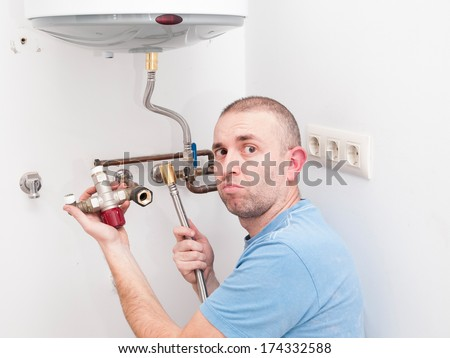 Inexperienced plumber trying to repair an electric water heater - stock photo