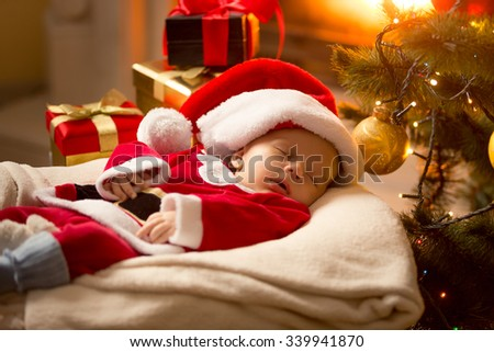 Infant baby boy in Santa costume sleeping at fireplace next to Christmas tree - stock photo
