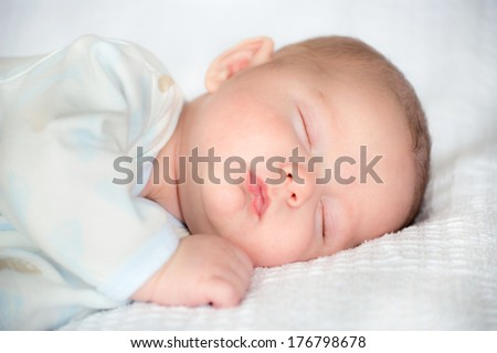 Infant baby boy sleeping peacefully - stock photo