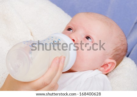 Infant baby feeding from bottle - stock photo
