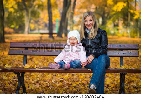 Infant baby girl in golden autumn park - stock photo